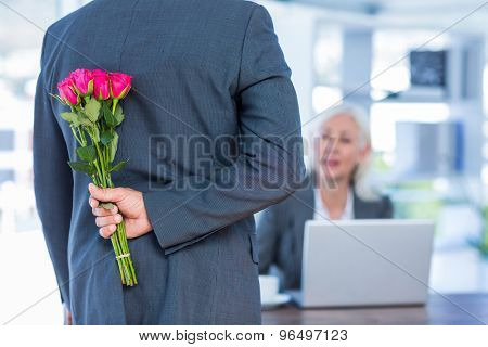 Businessman hiding flowers behind back for colleague in office