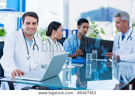 Happy doctor looking at camera while his colleagues looks at Xray in medical office