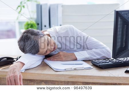 Tired businessman sleeping at her desk on the office
