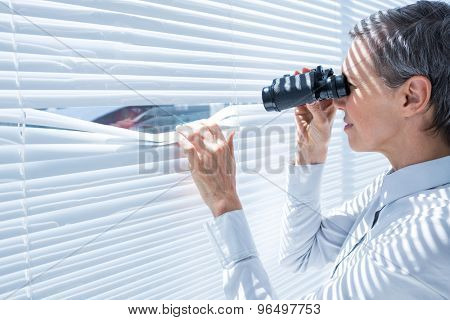 Side view of businesswoman looking through binoculars in the office