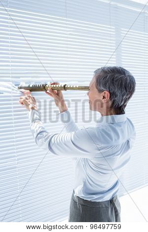 Side view of businesswoman looking through field-glass in the office