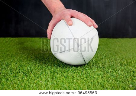 Rugby player posing a rugby ball on the grass