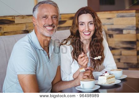 Casual couple having coffee and cake together at the coffee shop