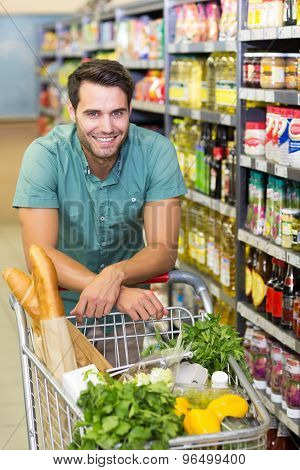 Portrait of smiling man buy product with his trolley at supermarket