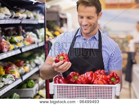 Smiling handsome worker taking a vegetable on her hand in suprmarket