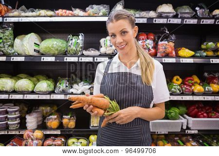 Pretty blonde woman holding carrot and looking at camera in supermarket