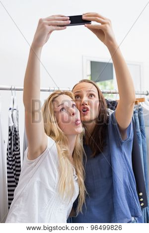 Happy friends taking a selfie while doing funny faces
