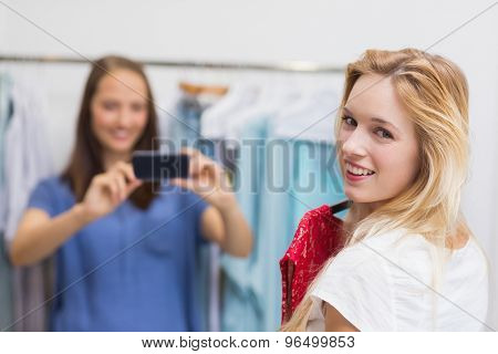Portrait of a pretty brunette photographing her friend