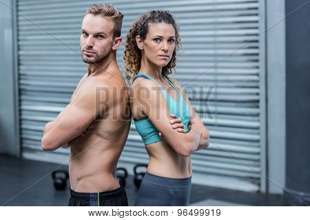 Portrait of an attentive muscular couple giving back to back