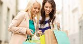 sale, shopping, tourism and happy people concept - two beautiful women looking inside shopping bags  poster