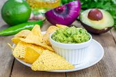 pic of nachos  - Cup with chunky guacamole served with nachos and ingredients on backgroung - JPG