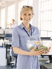 picture of fishbowl  - Blonde businesswoman holding small fishbowl in hand with a small goldfish - JPG