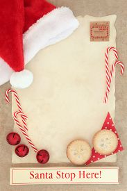 stock photo of letters to santa claus  - Christmas letter to santa claus with stop here sign on parchment paper with mince pies and decorations over brown paper background - JPG