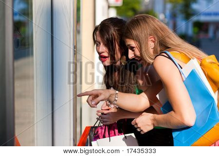 Two women being friends shopping downtown with colorful shopping bags, they are lolling into a glass store door and are amazed
