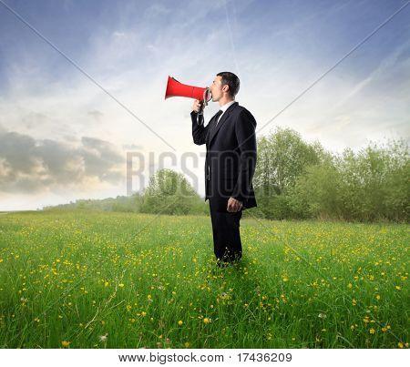 Empresário, falando em um megafone sobre um Prado Verde