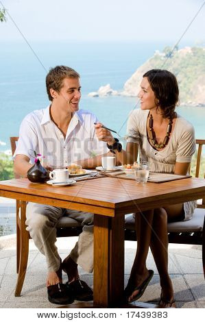 A young couple enjoying breakfast outside with an ocean backdrop