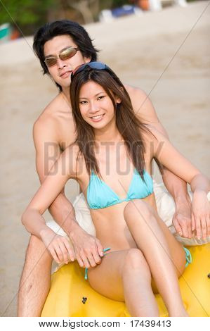 A young couple sitting on a kayak on the beach