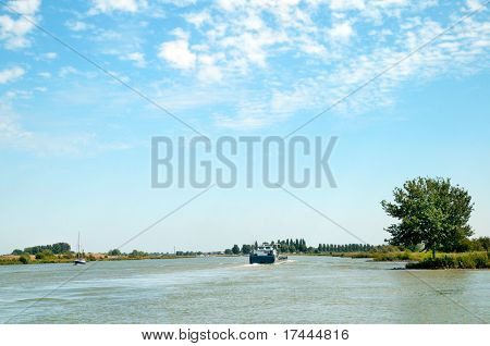 Landscape with river the Lek and cargo boat in Holland