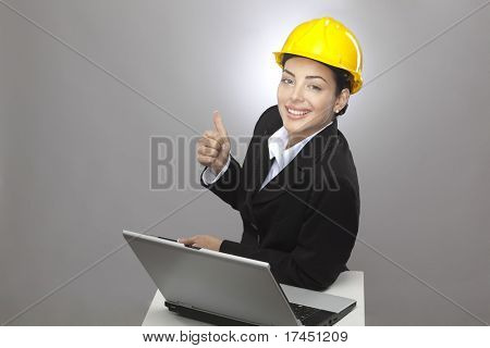 female architect with yellow safety hat showing thumb up