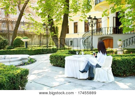Woman sitting at a cafe table in garden setting