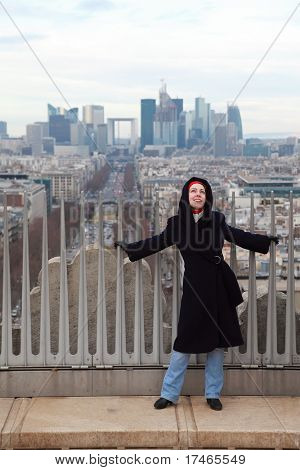 young woman standing on Triumfaly arch, view of La Defense in Paris, France
