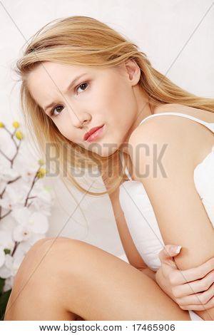 Mujer que tiene un dolor de estómago sentado en la cama