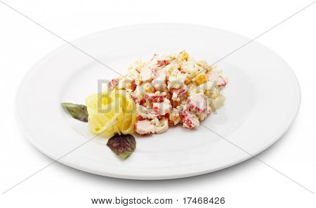 Salad Comprises Crab Meat, Rice, Pineapple and Corn Dressed with Lemon Slice (Abstract Flower) and Leaf of Basil. Isolated on White Background