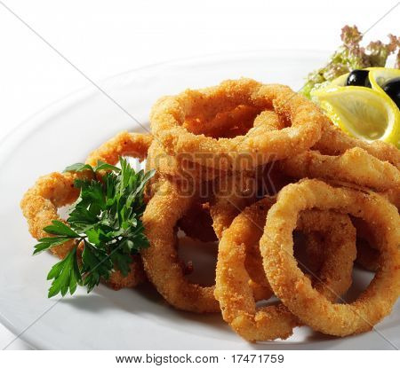 Seafood - Fried Calamari. Deep-fried Squid Dressed with Salad Leaves, Parsley, Olives and Lemon. Isolated on White Background