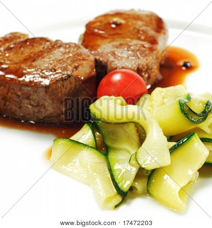 Veal Medallions with Zucchini and Cherry Tomato. Isolated on White Background
