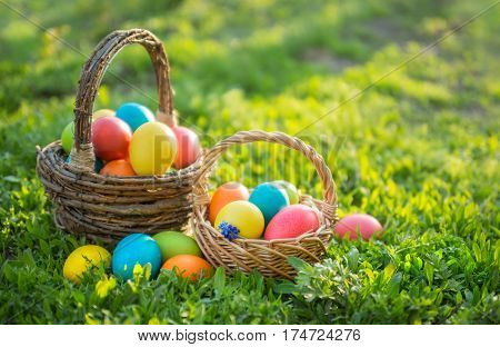 Happy Easter. Colorful Easter eggs in wicker baskets, in open air. Easter background with copyspace