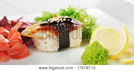Japanese Cuisine -  Eel (unagi) Nigiri Sushi with Ginger and Seaweed. Topped with Eel Sauce and Sesame