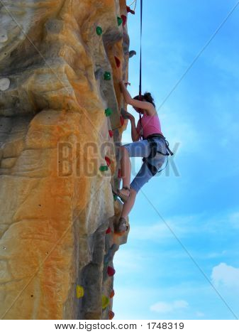 Active Teen Girl Climbing Artificial Rock