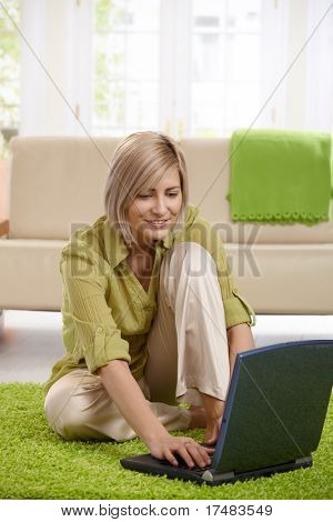 Smiling woman sitting on living room floor in front of sofa, working on laptop.?