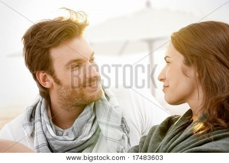 Young couple sitting on summer beach with blanket enjoying sunset, looking at each other, smiling.?