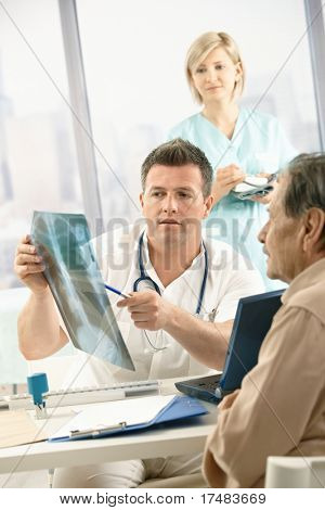 Doctor discussing diagnosis of x-ray image with older patient sitting in office, nurse in background.?