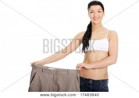 Young happy woman showing how much weight she lost. Isolated on white background