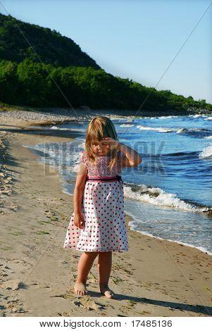 Unhappy little girl on the beach
