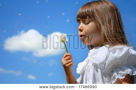 Kleines Mädchen bläst Löwenzahn, blauer Himmel und Herz Form Wolke in der backgound