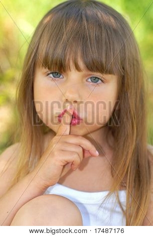 Small beautiful girl with a finger at her mouth
