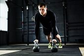 Intense workout in gym: male athlete performing kettlebell pushups looking determined and strained poster