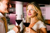 stock photo of red wine  - Man and woman in a hotel bar in the evening having glasses of red wine and a little flirt - JPG