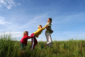 image of children playing  - Children playing in the grass on a bue sky background - JPG