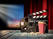 Retro film production accessories placed on wooden planks. Concept of film-making. Red curtain and m poster