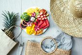 Fresh fruit plate and set of summer fashion beach accessories, top view from above (overhead). Tropi poster