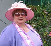 image of mad hatter  - A woman all decked out in her pink and lavender ragala is ready for an offical red hat tea party - JPG