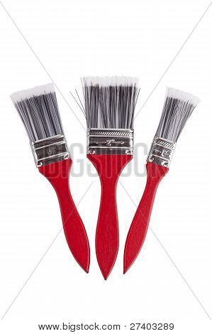 Three Paint Brushes Of Various Sizes On A White Background