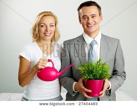 Photo of happy man with plant and woman holding watering pot looking at camera