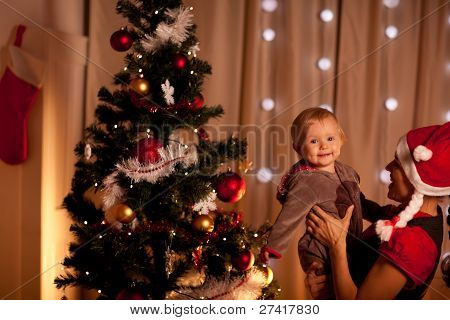 Portrait Of Lovely Baby On Mamas Hand Near Christmas Tree