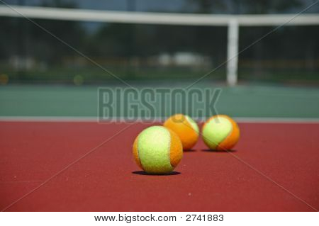 Multi-Colored Tennis Balls On Hard Court