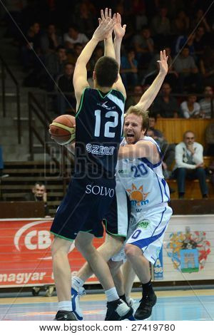 KAPOSVAR, HUNGARY - DECEMBER 10: Josh Wilson (in white) in action at a Hungarian Championship basketball game Kaposvar (white) vs. Szeged (blue) on December 10, 2011 in Kaposvar, Hungary.